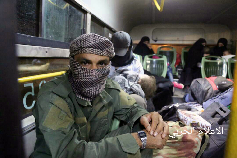 An al Qaida-linked militant sits in a bus after being evacuated Thursday from northeast Lebanon, part of a swap in which Syrian rebels would release political prisoners.