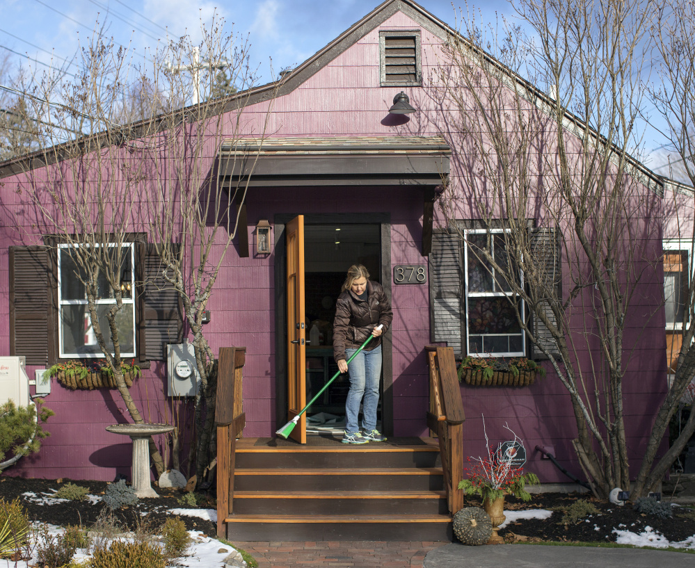 "Krista Desjarlais sweeps the steps at the Purple House in North Yarmouth last fall. It was named one of 50 finalists for Bon Appetit's ""Best New Restaurants in America."""