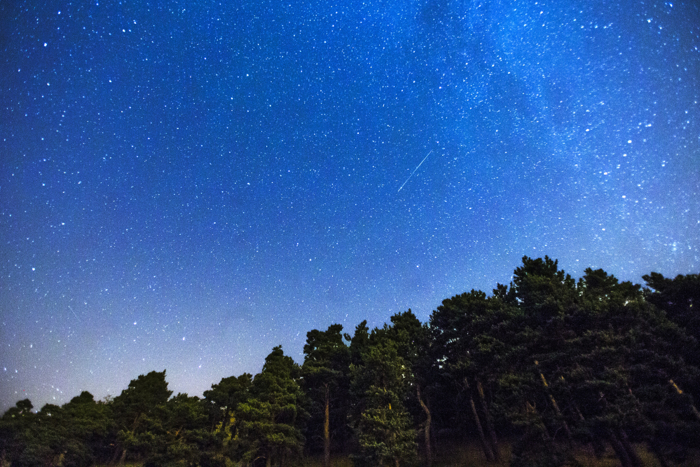 Two meteors, center and lower left, streak across the sky during the annual Perseid meteor shower in 2014.