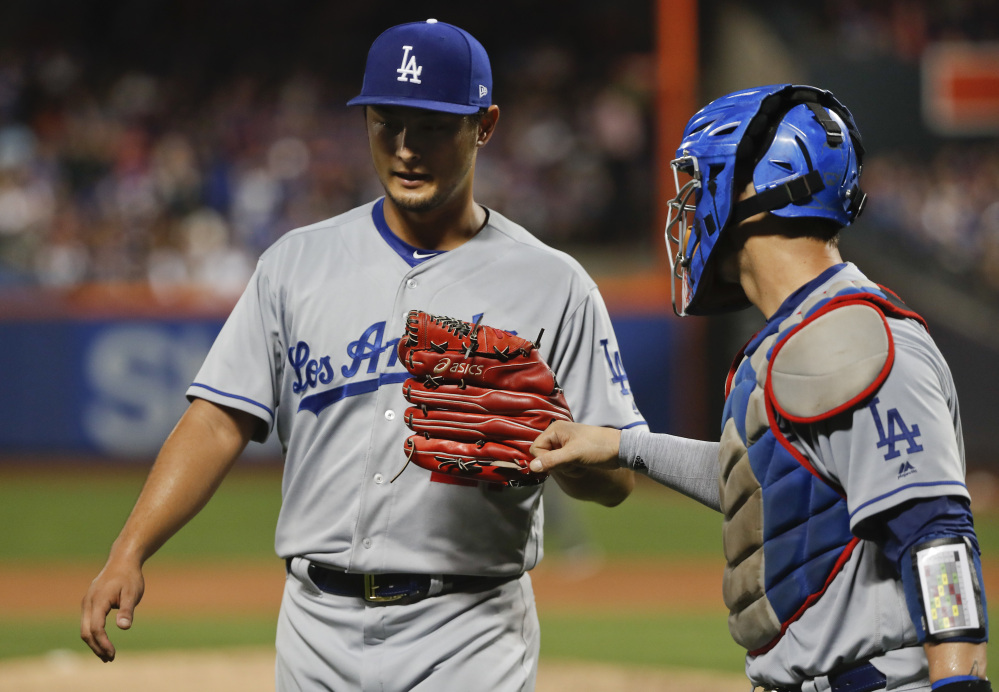 Los Angeles Dodgers starting pitcher Yu Darvish bumps fists with catcher Yasmani Grandal at the end of the third inning Friday en route to a victory over the host New York Mets.