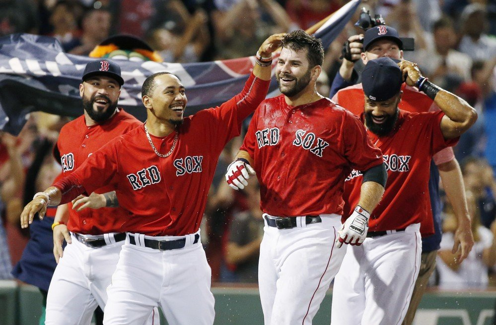 Boston's Mitch Moreland, center right, celebrates his walk-off home run with teammates, including Mookie Betts, second from left, in the 11th inning Friday night at Fenway Park.