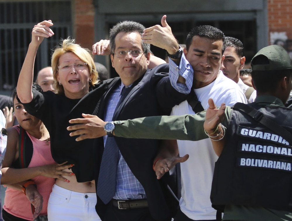 Venezuelan General Prosecutor Luisa Ortega Diaz, left, is surrounded by loyal employees after she was barred from entering by security forces, outside of the headquarters in Caracas, Venezuela.