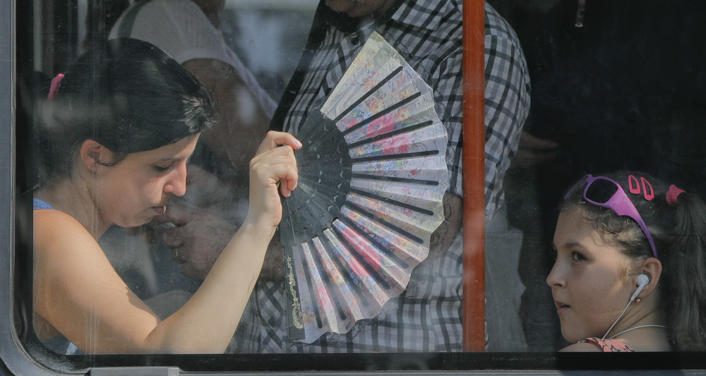 """A woman uses a fan to cool herself and a child while ridding a tram in Bucharest, Romania, on Friday. Meteorologists there issued a """"red code"""" heat alert for the next two days."""