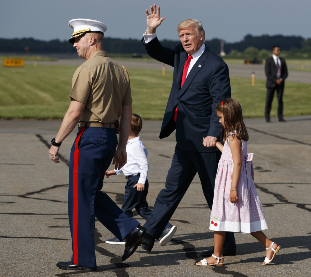President Trump waves after arriving at Morristown Municipal Airport with grandchildren Arabella Kushner, right, and Joseph Kushner to begin a vacation at his Bedminster golf club on Friday, in Morristown, N.J. His staff will cycle in and out over the next 17 days.