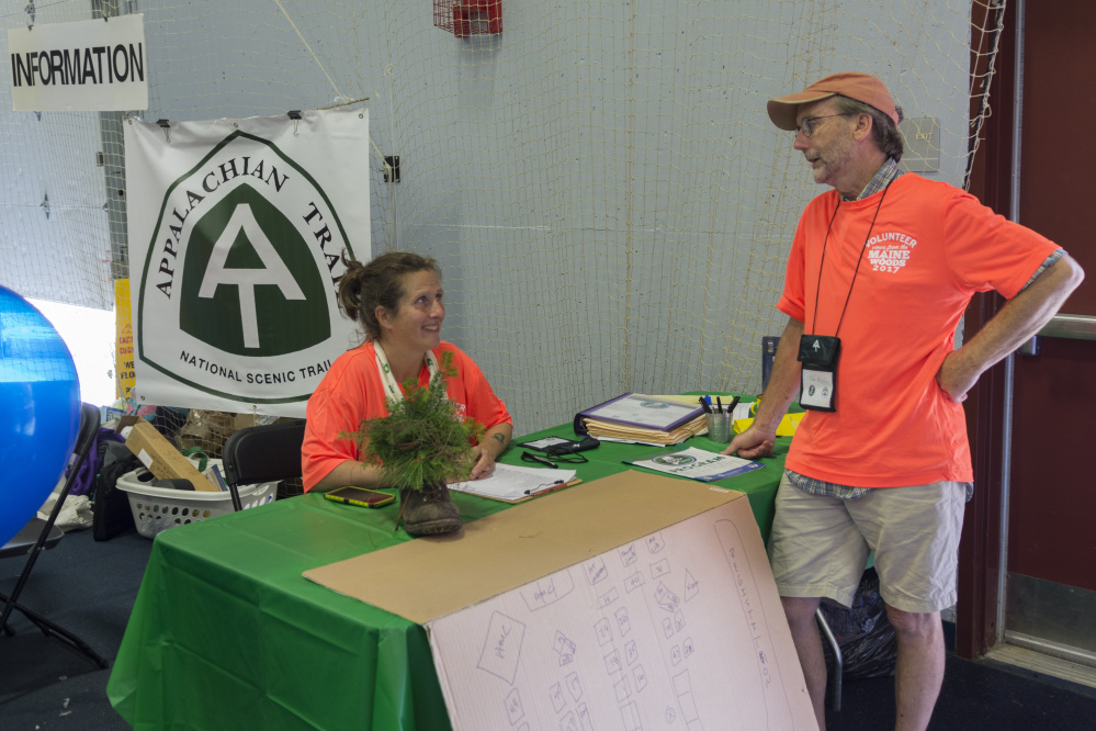 Holly Sheehan, who manages the Maine Appalachian Trail Club's Caretaker & Ridgerunner Education Program, and Tony Mullin confer during registration Friday at the Appalachian Trail Conservancy Conference at Colby College in Waterville. Sheehan and Mullin provided directions to participants arriving at the conference.
