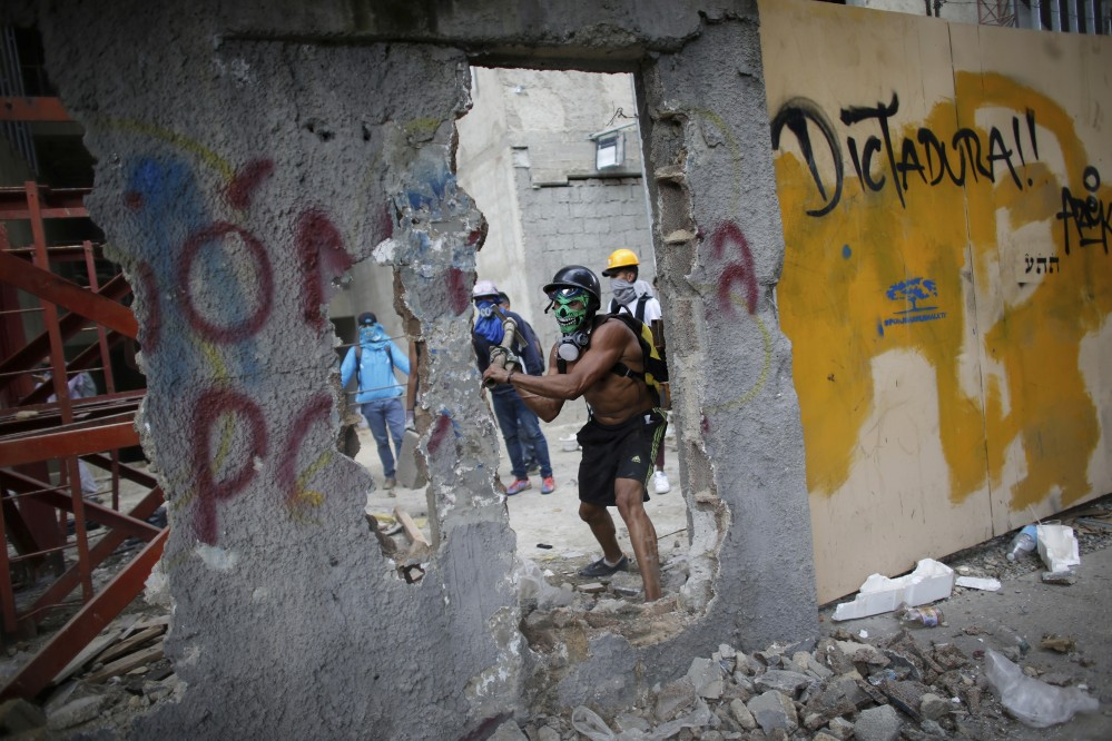 An anti-government demonstrator whacks a wall to release pieces of concrete to throw at Venezuelan Bolivarian National Police.