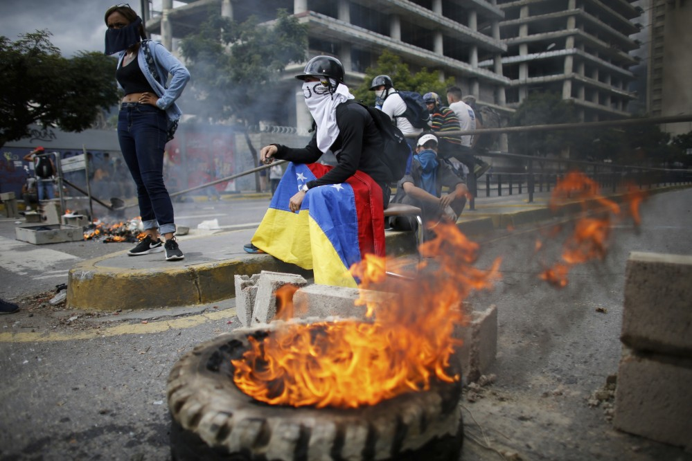 Masked anti-government demonstrators stand next to a burning barricade during a protest against the installation of a constitutional assembly Friday in Caracas, Venezuela.