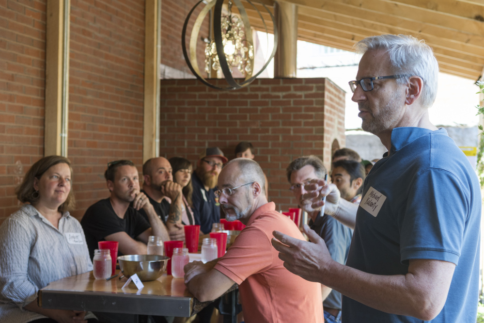 Michael Kalanty, author and sensory scientist, introduces himself to the blind taste test participants Wednesday at the Somerset Grist Mill in Skowhegan.