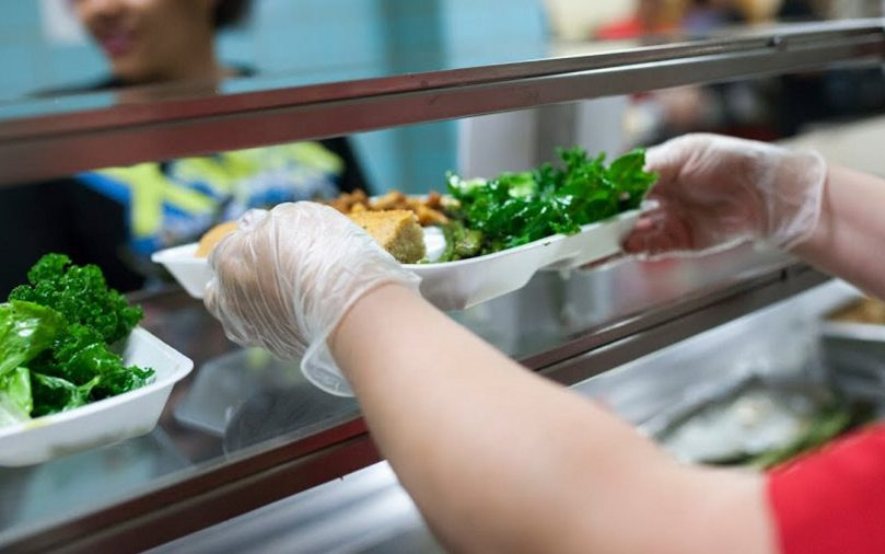 Food service staff at a Delaware high school serve a locally sourced lunch, including kale, in 2015. Only about one percent of the USDA's $19 billion school nutrition budget goes toward introducing fresh produce.