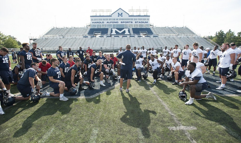 UMaine football coach Joe Harasymiak gathers his team for a post-practice talk Wednesday at Morse Field on the Orono campus. The second-year coach doesn't have a starting quarterback yet, and doesn't know whether he'll have three of his best players available.