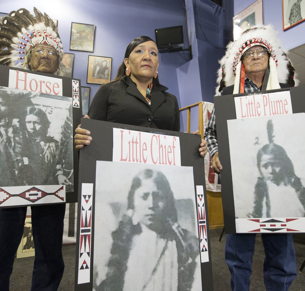 Yufna Soldier Wolf, center, of the Northern Arapaho, with tribal elders Mark Soldier Wolf, left, and Crawford White Sr., right, hold pictures of the three Arapaho children buried at the Carlisle Indian School, now the Army War College.