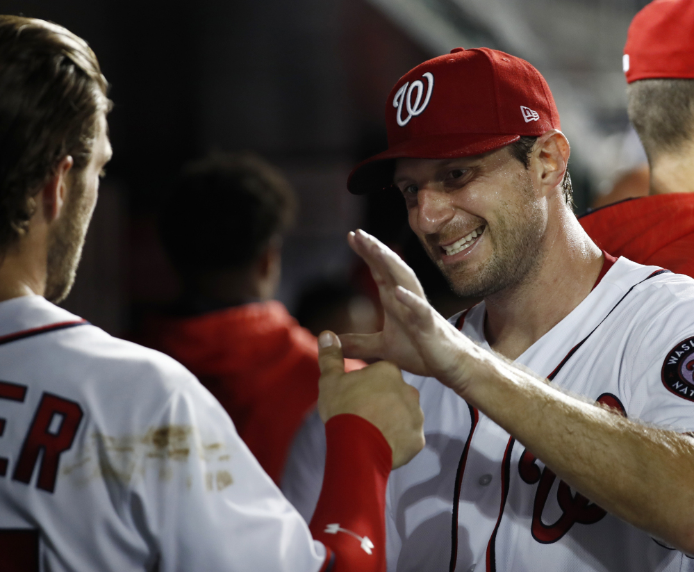 Max Scherzer, right, celebrates with Bryce Harper after coming off the field in the seventh inning of the Nationals' 3-2 win over Miami on Monday. Scherzer pitched seven innings and Harper homered in the win.