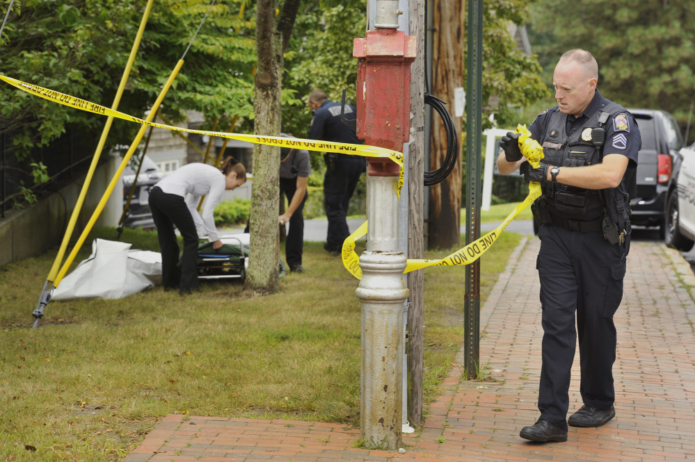 Portland police Sgt. Charles Libby removes police tape as medical staff and fellow officers prepare to remove the body of a man found at the intersection of Danforth and Vaughan streets in Portland on Tuesday morning. The death did not appear to be suspicious, police say.