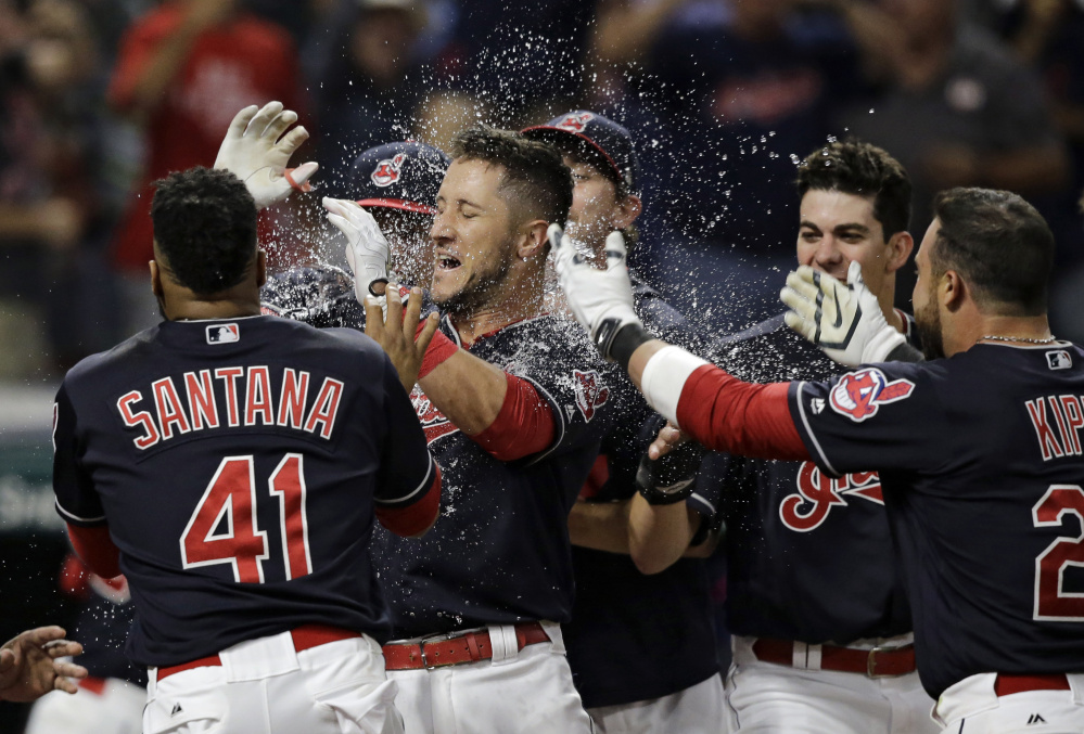 Yan Gomes, center, is mobbed by teammates Tuesday night after hitting a game-ending three-run homer to give the Cleveland Indians a 4-1 victory at home against the Colorado Rockies.