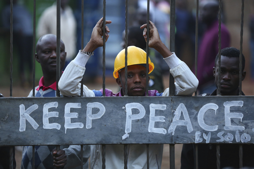Kenyans in Kibera, Nairobi, lock themselves behind a gate with a Keep Peace sign as others burn tires to protest in support of opposition leader and presidential candidate Raila Odinga on Wednesday.