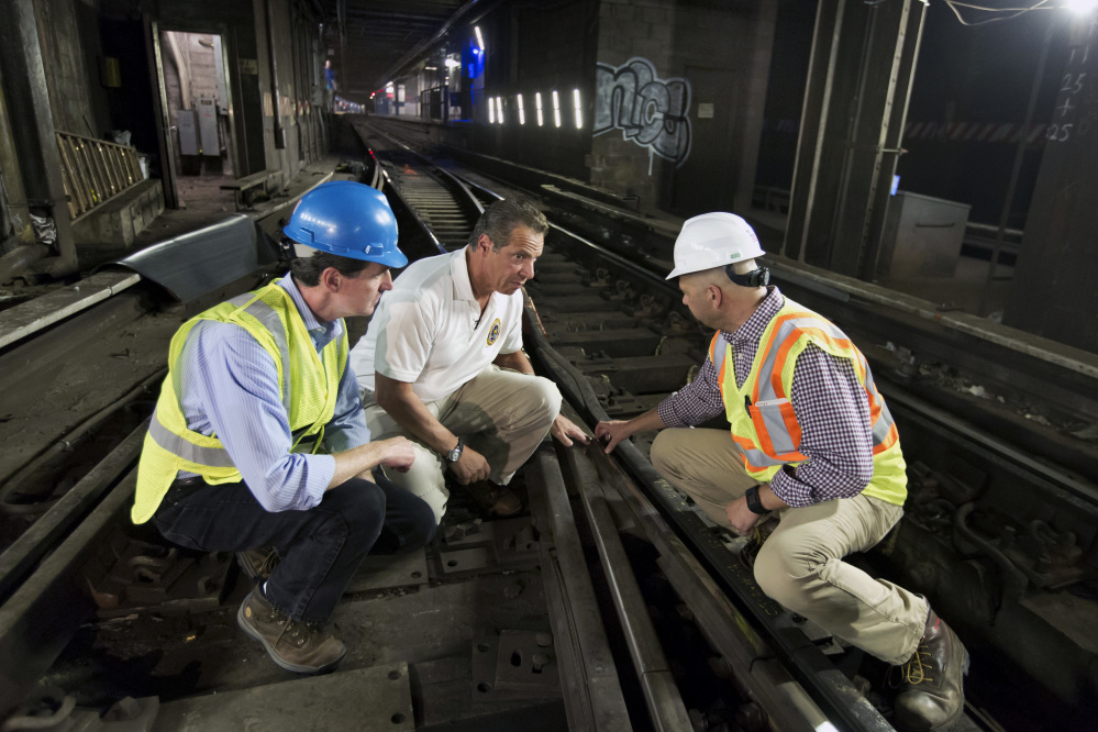 ConEd CEO John McAvoy, left, Gov. Andrew Cuomo, center, and an infrastructure company official examine tracks during a media tour of a section of the New York City subway system.