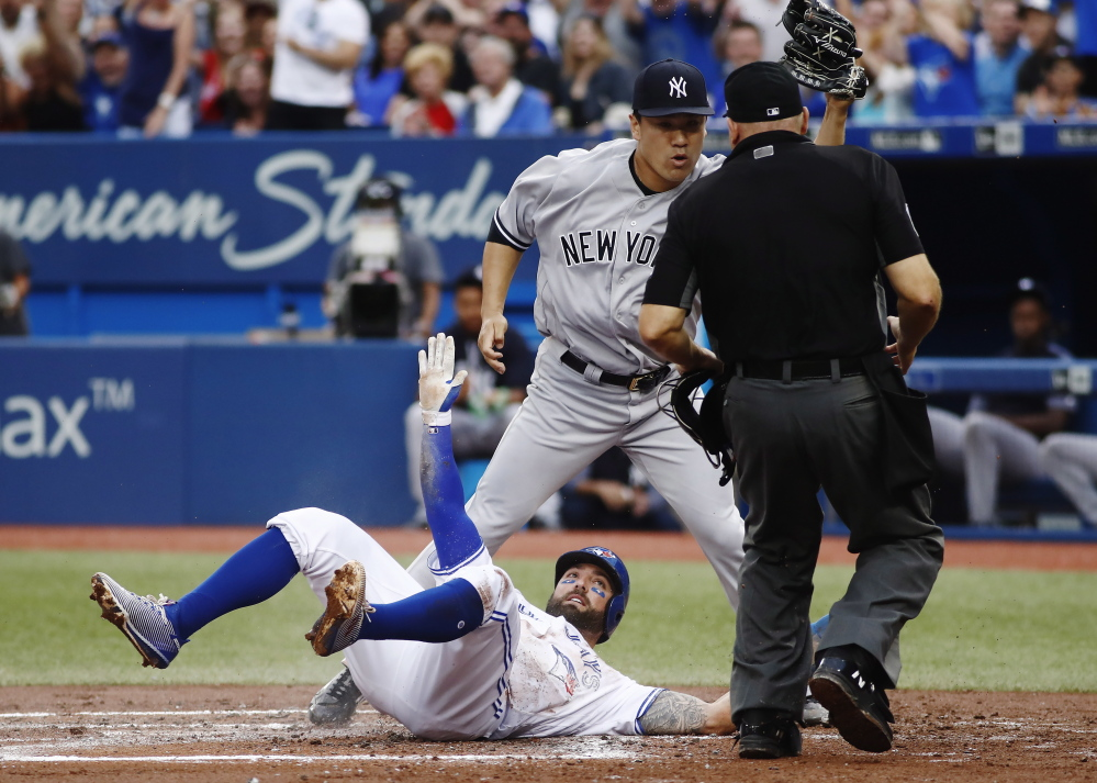 Kevin Pillar of the Toronto Blue Jays is out at the plate Wednesday night, tagged by pitcher Masahiro Tanaka of the New York Yankees after being caught in a rundown.