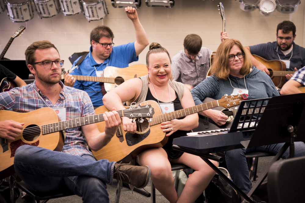 Brittany Genness, center, a music teacher at Lawrence High School, smiles at the completion of a practice piece during the Kids Rock music program at Waterville High School on Wednesday. The program, hosted by the Maine Department of Education, encourages kids in grades K-12 to participate in music programs.