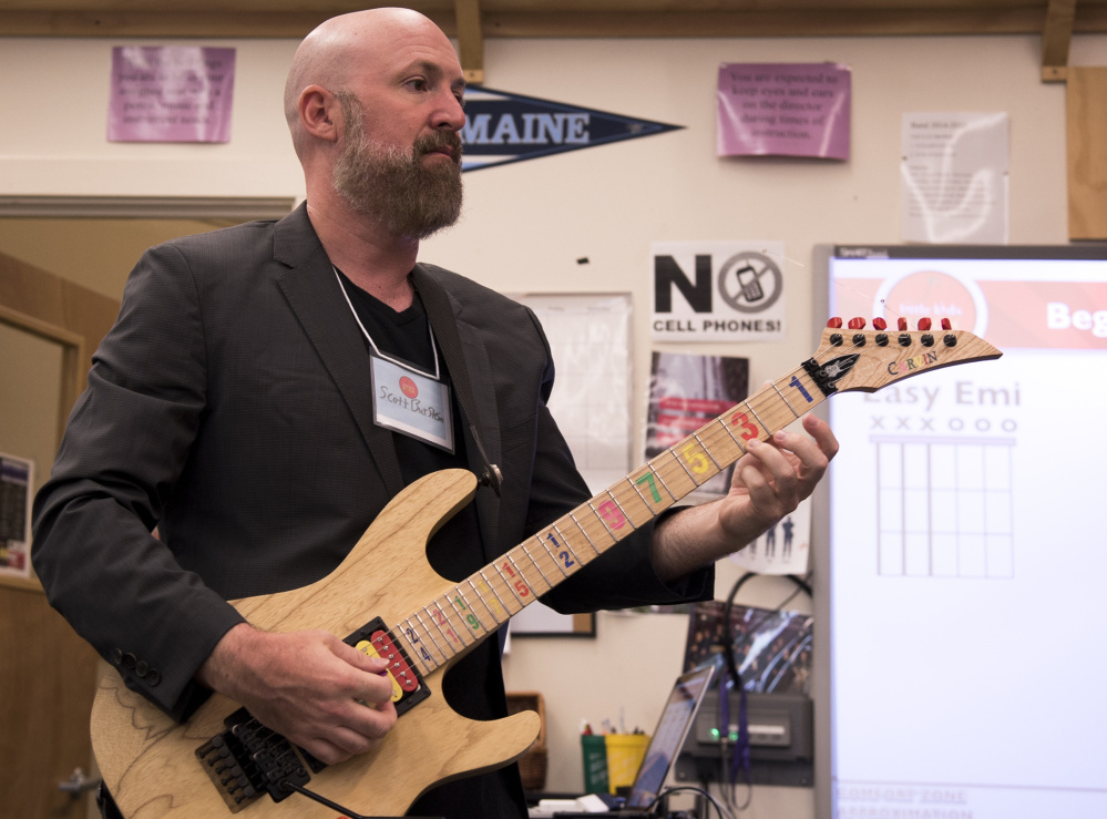 Scott Burstein, director of training and learning with the organization Little Kids Rock, demonstrates chords at a teacher training at Waterville Senior High School on Wednesday.