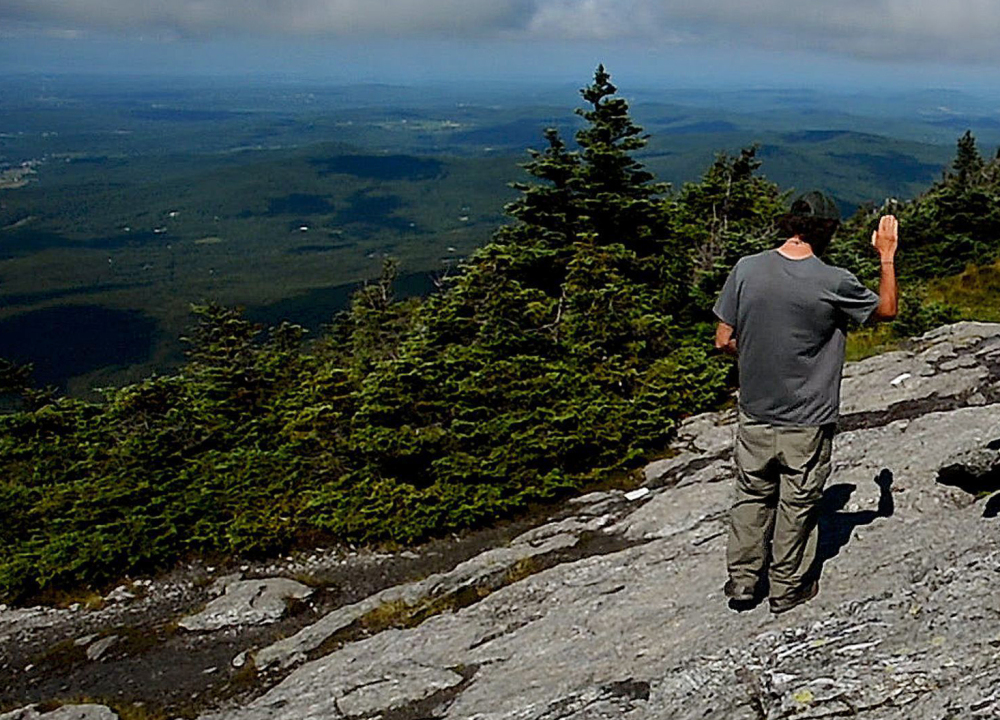 "Adam Joseph of the Green Mountain Club talks to hikers new to Vermont's Mount Mansfield in July. ""It's everywhere up there,"" Joseph said of cremation ashes on another peak in Camels Hump State Park. Vermont's cremation rate was nearly 70 percent in 2016."