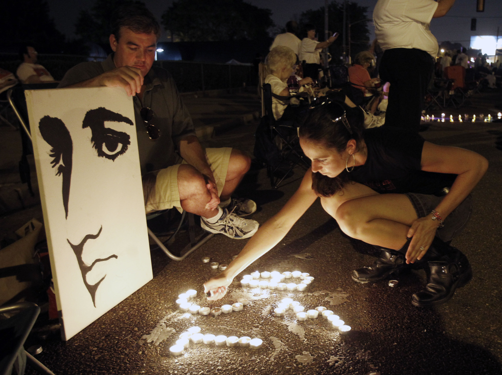 Fans light candles at an Elvis Presley display in front of Graceland on Aug. 15, 2010.