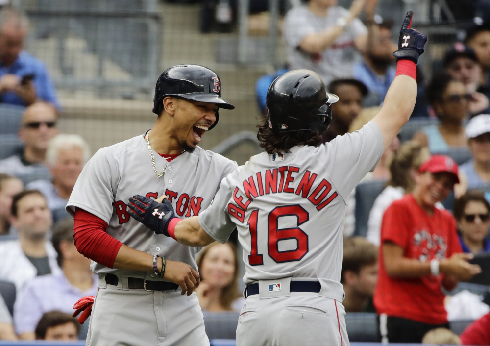 Boston's Mookie Betts, left, celebrates with Andrew Benintendi after Benintendi hit a three-run home run during the third inning Sunday against the Yankees in New York. Benintendi had a pair of three-run homers for the Red Sox.