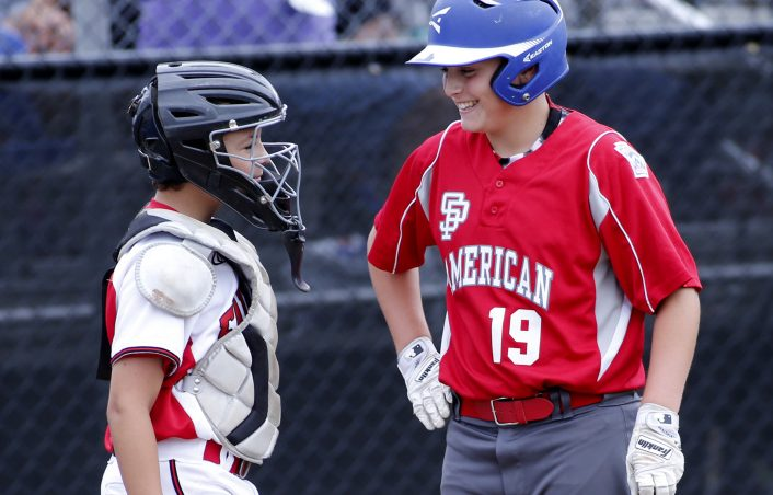 Nolan Hobbs of South Portland American shares a laugh with Connecticut catcher Aiden Rivera.  (Staff photo by Derek Davis)