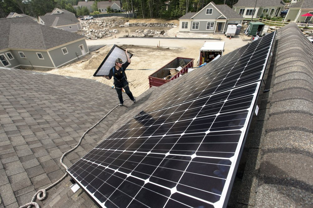 "Jack Doherty, photovoltaic project manager for ReVision Energy, carries a solar panel to the roof ridge of a home at OceanView at Falmouth. Though there's frustration, ""facts do matter and they will eventually prevail,"" said James Cote, a lobbyist who represents an alliance of solar installers."