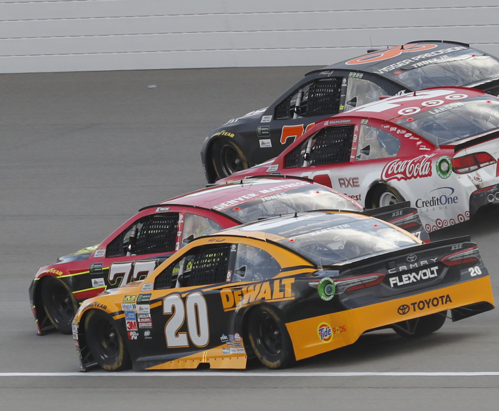Matt Kenseth, front, Erik Jones, Kyle Larson and Martin Truex Jr. head into Turn 1 on an overtime restart Sunday in Brooklyn, Mich. Larson won for the third time this year.