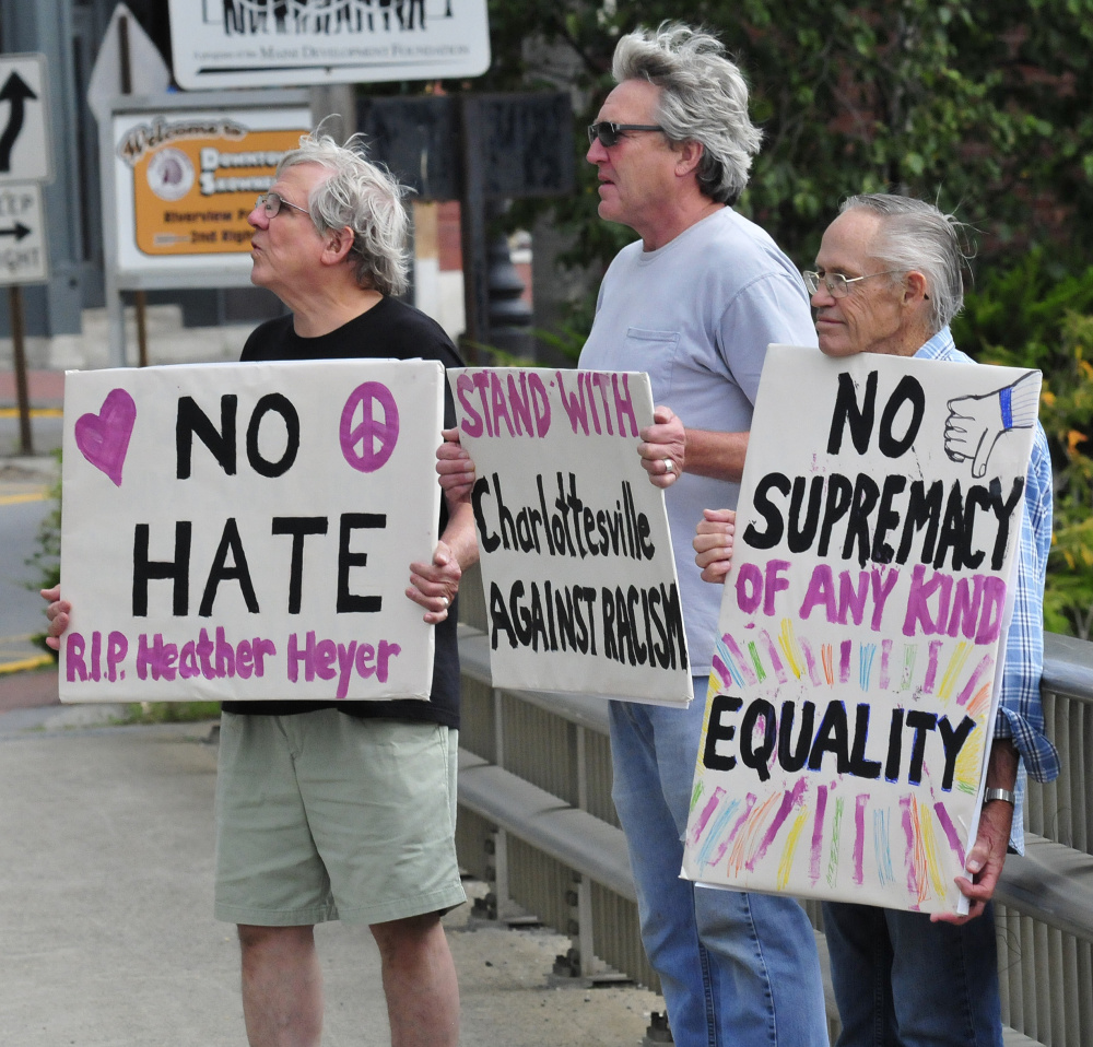 Protesters with Stand With Charlottesville Against White Supremacy hold signs Sunday. From left are Mark Roman, Greg Williams and Dale Riddle.