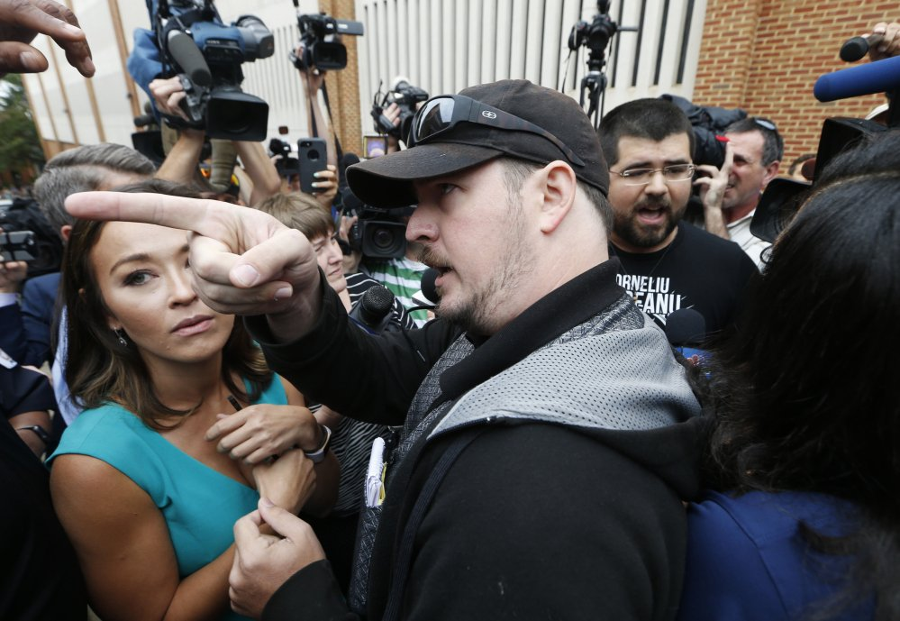 An unidentified man voices his displeasure at the media after a court hearing for James Alex Fields Jr. in front of court in Charlottesville, Va., on Monday. A judge has denied bond for Fields, who is accused of plowing his car into a crowd at a white nationalist rally on Saturday.