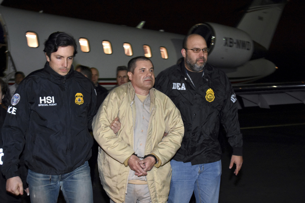 "Authorities escort Joaquin ""El Chapo"" Guzman from a plane at an airport in New York in January. Guzman is seeking to have his public defenders replaced by private lawyers, but questions remain about how they will get paid."