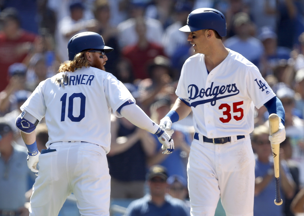 Los Angeles Dodgers' Justin Turner, left, celebrates his solo home run with Cody Bellinger during the eighth inning of a baseball game against the San Diego Padres in Los Angeles, Sunday, Aug. 13, 2017. (AP Photo/Alex Gallardo)