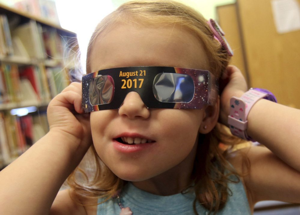 A girl tries on eclipse glasses at a library in Kings Mountain, N.C., on Wednesday. Glasses were being given away while they lasted.