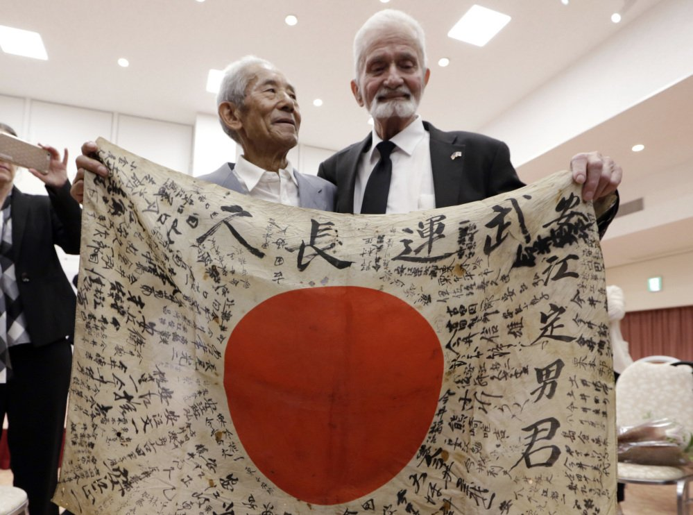 WWII veteran Marvin Strombo, right, and Tatsuya Yasue, 89, hold a Japanese flag that was owned by his brother Sadao Yasue, who was killed during World Work II