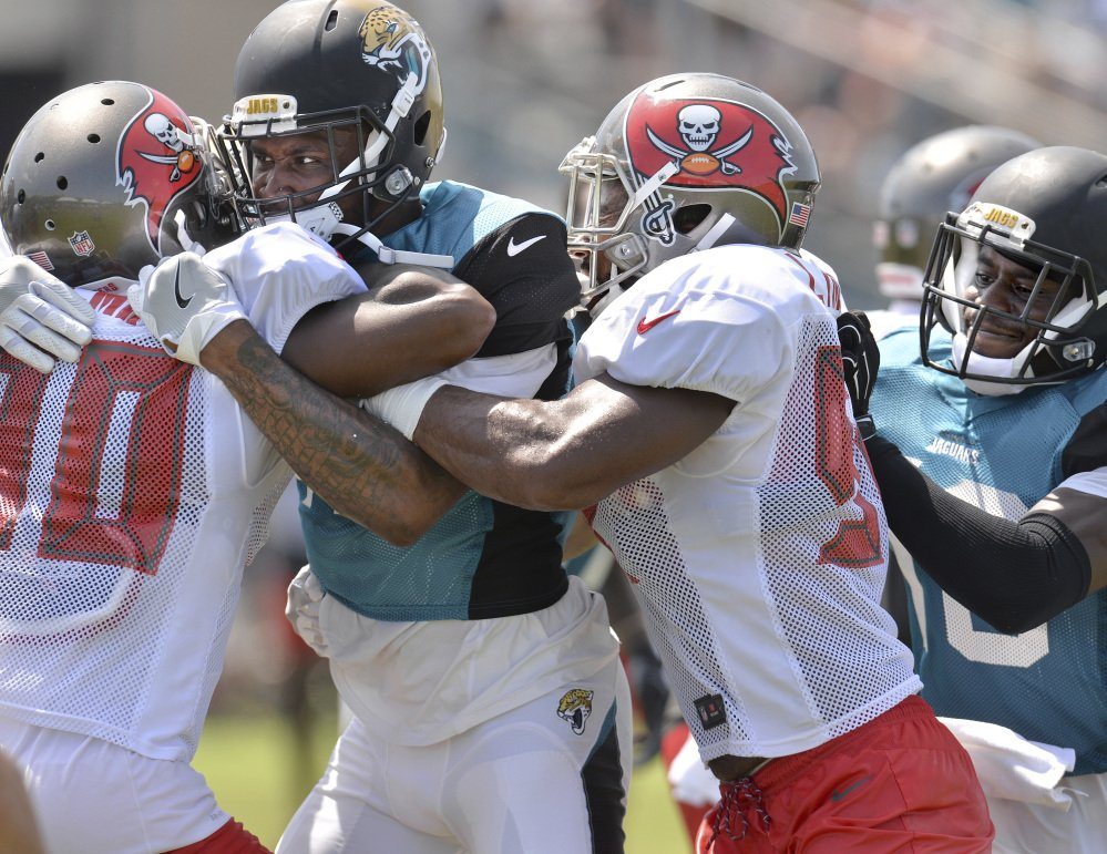 Things weren't entirely rosy Tuesday when the Tampa Bay Buccaneers held a joint practice with the Jacksonville Jaguars. Maurice Fleming of Tampa Bay, left, is grabbed by Jamal Robinson of Jacksonville.