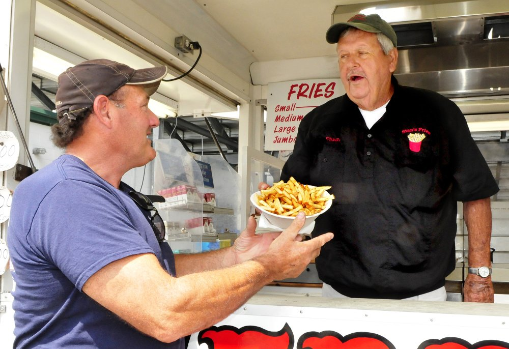 "Stanley McGray, right, hands a jumbo order of fries to Mike McCourt at his Stan's French Fries stand at the Skowhegan State Fair on Tuesday. McCourt said he has enjoyed Stan's fries for decades. ""I buy them here all the time cause I like the way they cook them,"" McCourt said."