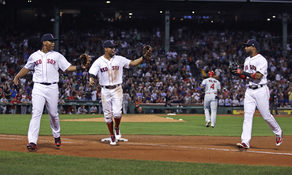 From left, Boston Red Sox third baseman Rafael Devers, shortstop Xander Bogaerts and second baseman Eduardo Nunez, celebrate after turning a triple play on a ground out by St. Louis Cardinals' Yadier Molina during the fourth inning Tuesday in Boston.