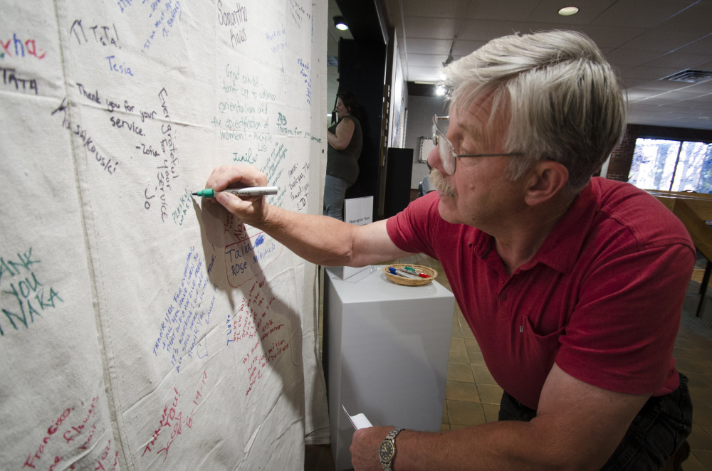 "Vietnam War veteran Richard Sevigny, of North Waterboro, signs his name and adds ""Pleikn, Vietnam, I was there, '66-'67"" to a banner of remembrance at a Welcome Home ceremony held Thursday at the University of Maine at Augusta. The event was organized by the Bureau of Veteran's Affairs."