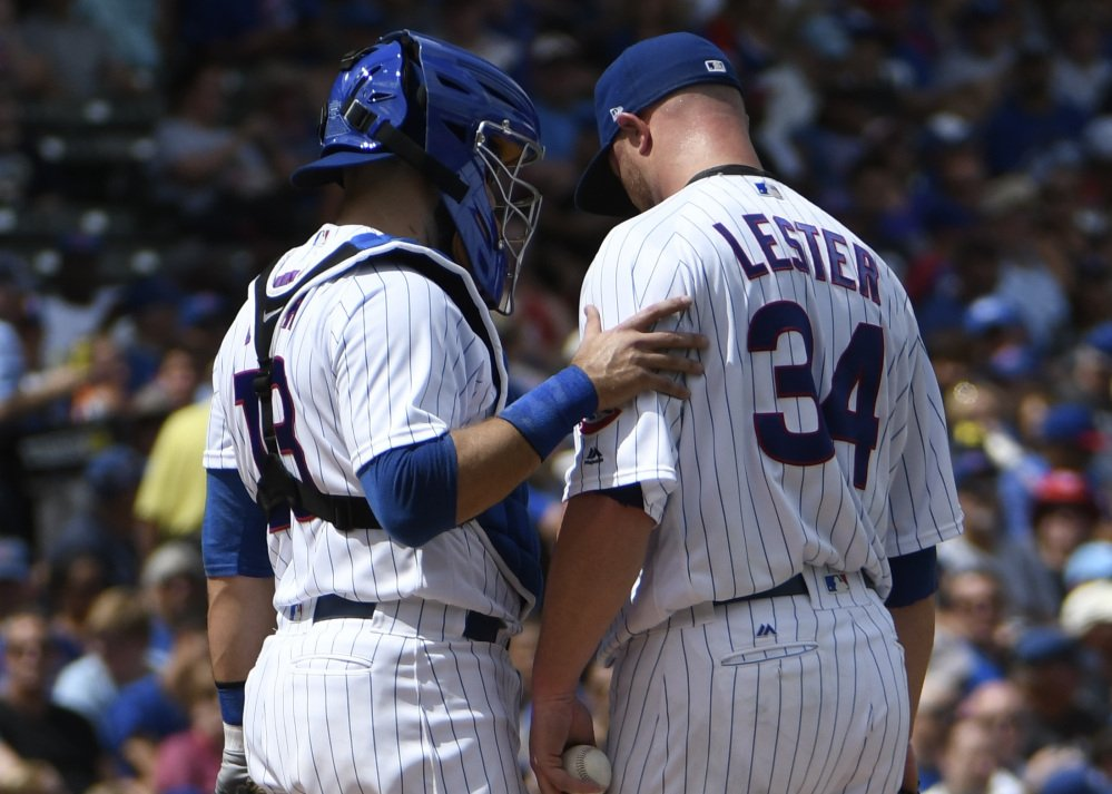 Cubs catcher Alex Avila, left, talks with starting pitcher Jon Lester in the second inning Thursday. Lester left the game with left lat tightness having allowed nine runs in the inning.