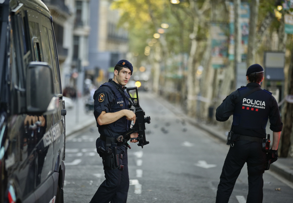 Armed police officers patrol a deserted street in Las Ramblas, in Barcelona, Spain, on Friday, a day after the driver of a white van sped down a pedestrian zone there, killing 13 people and wounding scores.
