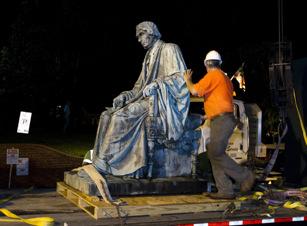 Workers sits the monument dedicated to U.S. Supreme Court Chief Justice Roger Brooke Taney on a flatbed truck after it was removed from outside the Maryland State House, in Annapolis, Md., early Friday, Aug. 18, 2017. Maryland workers hauled several monuments away, days after a white nationalist rally in Charlottesville, Virginia, turned deadly.