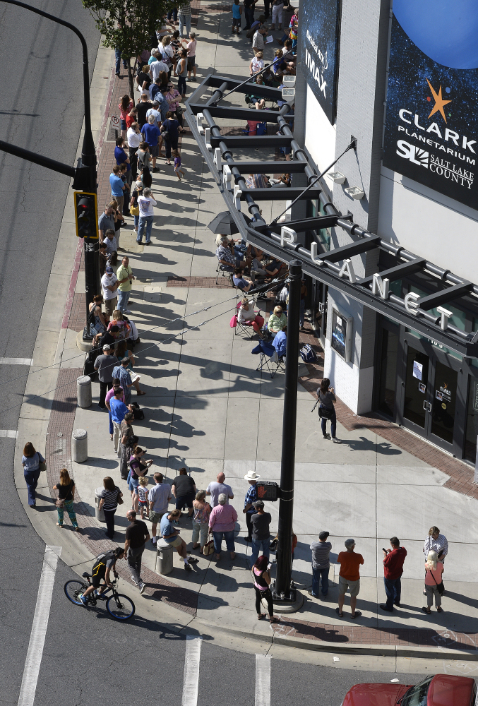 Hopeful eclipse-watchers line up outside the Clark Planetarium in Salt Lake City to get eclipse glasses from the gift shop Thursday. Eclipse mania is building and so is demand for the glasses that make it safe to view the first total solar eclipse to cross the U.S. in 99 years.