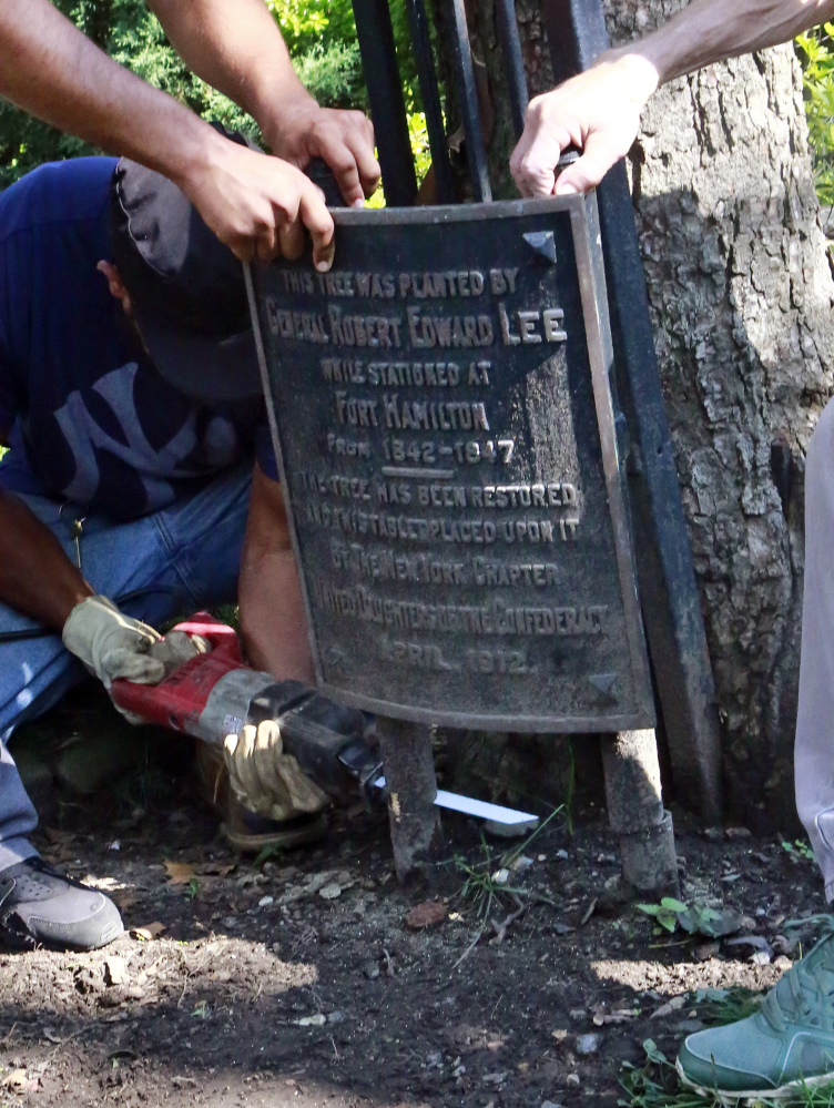 Workers remove two plaques honoring Gen. Robert E. Lee from the property of St. John's Episcopal Church in Brooklyn, New York, in the wake of last weekend's deadly white nationalist rally in Charlottesville, Virginia.