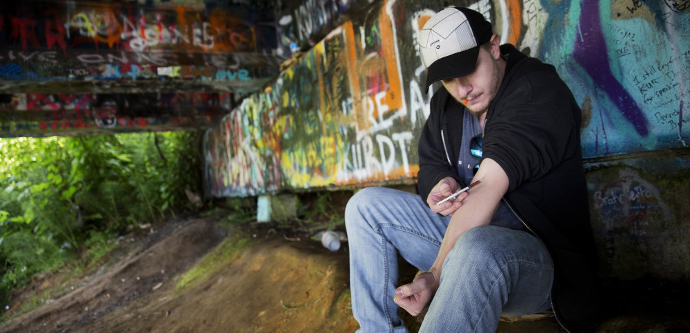 Forrest Wood, 24, injects heroin into his arm under a bridge along the Wishkah River at Kurt Cobain Memorial Park in Aberdeen. Wood grew up here, watching drugs take hold of his relatives, and he swore to himself that he would get out. But he started taking opioid painkillers as a teenager, and before he knew it he was shooting heroin.