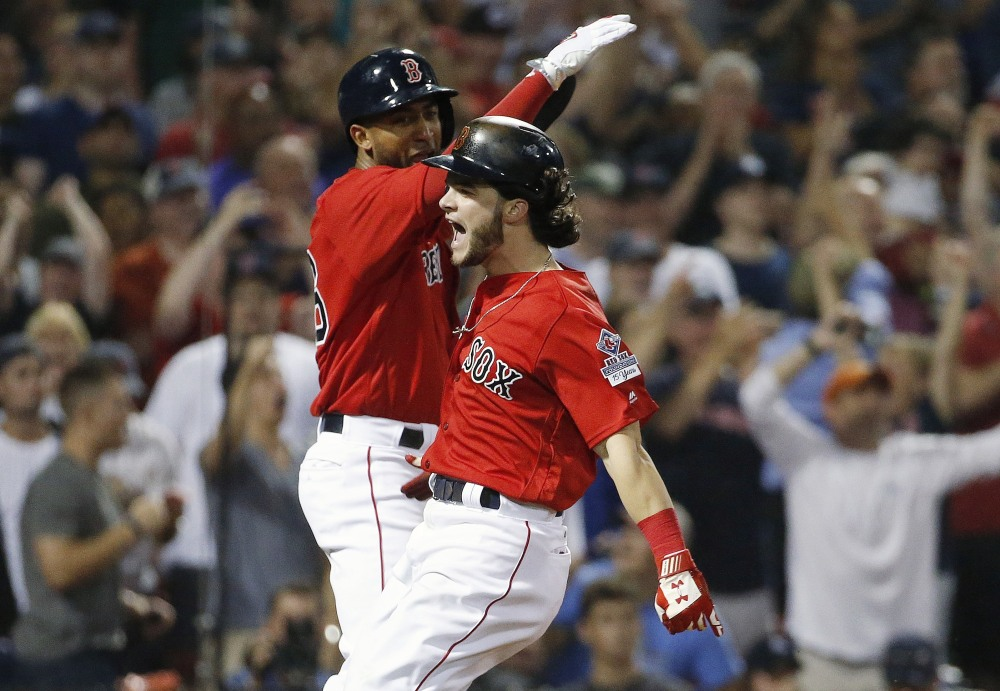 Boston's Andrew Benintendi, right, and Eduardo Nunez celebrate after scoring on a two-run single by Mitch Moreland in the seventh inning Friday night against the Yankees at Fenway Park.