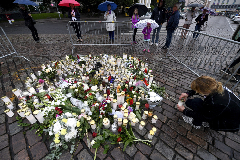 A woman places a candle Saturday by floral tributes to the victims of a stabbing attack in Turku, Finland, on Friday that killed two people.