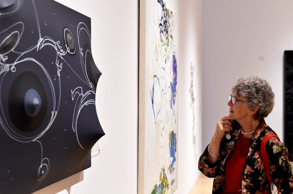 Suzanne Rankin inspects a piece of artwork at the Colby College Museum of Art. A member of the Colby family, Rankin came to Saturday's reunion from Wisconsin.