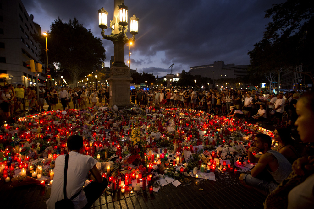 People gather around a makeshift memorial to terror attack victims in Barcelona on Sunday.