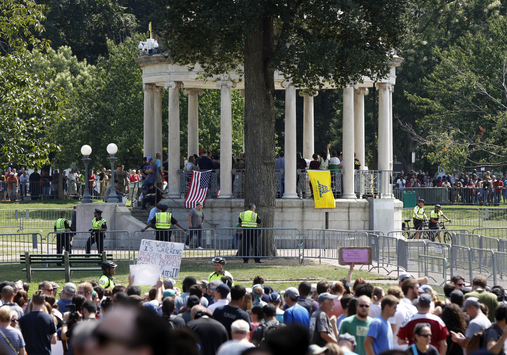 "Organizers gather on a bandstand on Boston Common during a ""free speech"" rally staged by conservative activists Saturday. Counterprotesters line barricades ringing the bandstand."